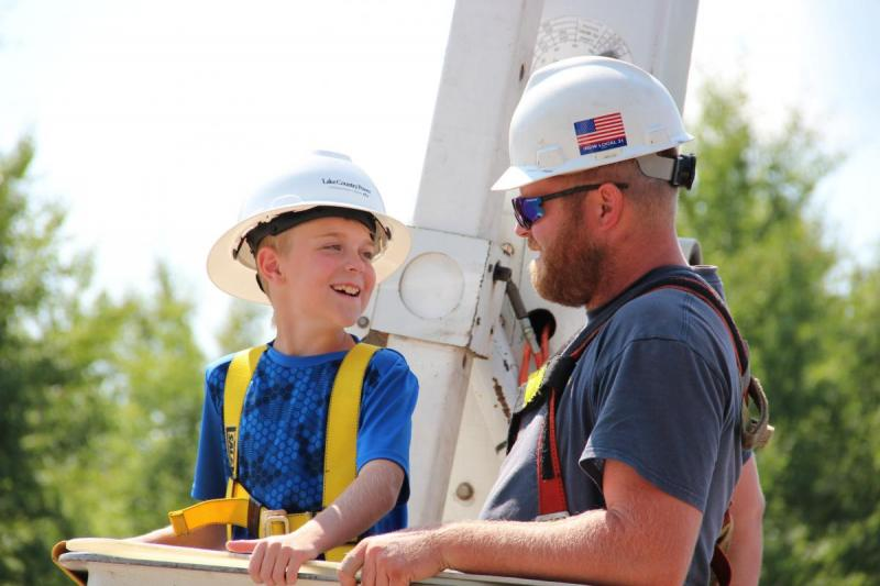 Lineman with boy in bucket truck